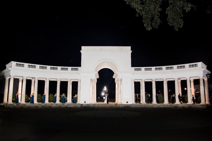 Image of the Colonnade at night with bride and  groom under the arches and bridesmaids and men under the columns - outdoor wedding venues - lafayette la - Le Pavillon